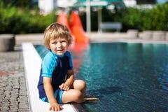 使用用水的逗人喜爱的小孩由室外游泳池 免版税图库摄影