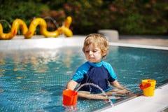 使用用水的逗人喜爱的小孩由室外游泳池 库存图片