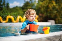 使用用水的逗人喜爱的小孩由室外游泳池 免版税库存图片