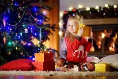 使用由一个壁炉的愉快的小女孩佩带的圣诞节睡衣在自圣诞前夕的一个舒适黑暗的客厅 免版税库存图片
