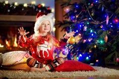 使用由一个壁炉的愉快的小女孩佩带的圣诞节睡衣在自圣诞前夕的一个舒适黑暗的客厅 免版税库存照片