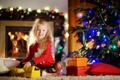 使用由一个壁炉的愉快的小女孩佩带的圣诞节睡衣在自圣诞前夕的一个舒适黑暗的客厅 免版税图库摄影