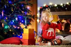 使用由一个壁炉的愉快的小女孩佩带的圣诞节睡衣在自圣诞前夕的一个舒适黑暗的客厅 库存照片