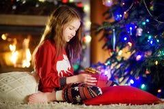 使用由一个壁炉的愉快的小女孩佩带的圣诞节睡衣在自圣诞前夕的一个舒适黑暗的客厅 库存图片