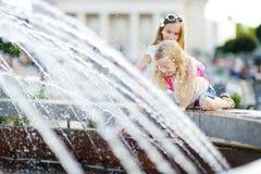 使用由城市喷泉的两个逗人喜爱的小女孩在热和晴朗的夏日 孩子获得乐趣用水在夏天 库存照片