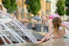 使用由城市喷泉的两个逗人喜爱的小女孩在热和晴朗的夏日 孩子获得乐趣用水在夏天 免版税库存照片