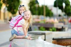 使用由城市喷泉的两个逗人喜爱的小女孩在热和晴朗的夏日 孩子获得乐趣用水在夏天 免版税库存图片