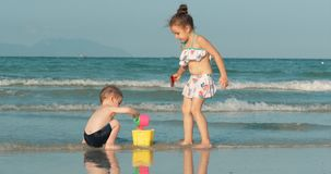 使用由有沙子的海的愉快和无忧无虑的孩子 由海的儿童游戏,兄弟和姐妹戏剧 ?? 股票视频