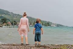 使用由湖的小孩在一个非常大风天在夏天雨下 图库摄影