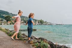 使用由湖的小孩在一个非常大风天在夏天雨下 免版税库存照片