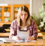 使用电子片剂的十几岁的女孩在图书馆 库存图片