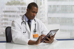 使用电子片剂的非裔美国人的医生,水平 免版税库存照片