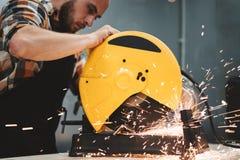 使用电子磨床的有胡子的工作者在服务站 在行动的工作 火花分开飞行 免版税库存照片