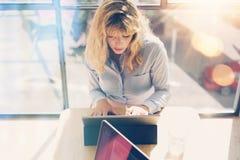 使用电子触板计算机的年轻美丽的女商人在晴朗的办公室 在弄脏的全景窗口 免版税库存照片