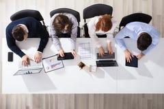 使用电子设备的商人在书桌 库存图片