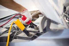 使用电池充电的跨接电线的汽车修理师人一个用完的电池 手充电的汽车电池的关闭有红色的电的和 免版税库存照片