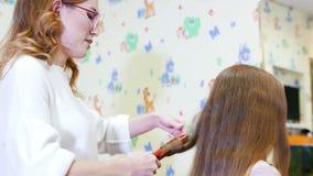 使用电烫发钳,美发师卷曲孩子女孩的长的头发, 股票录像