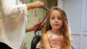 使用电烫发钳,美发师卷曲小逗人喜爱的女孩的长的头发, 滑子射击 股票录像