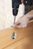 使用电螺丝,木匠登上门闩和锁处理门 库存照片