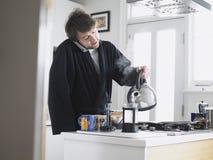 使用电话倾吐的水的人入咖啡柱塞 免版税库存照片