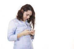 使用电话和微笑的妇女 免版税库存照片