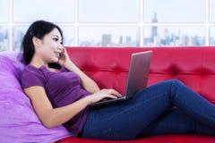 使用电话和膝上型计算机的亚裔女性在公寓 免版税库存图片