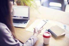 使用电话和膝上型计算机的女实业家,当坐在他的现代顶楼办公室时 工作移动设备的青年人的概念 免版税库存图片