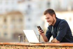 使用电话和膝上型计算机的愉快的人在阳台上 免版税库存照片