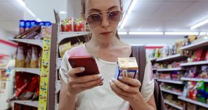 使用电话复选框的年轻女人在商店 股票录像