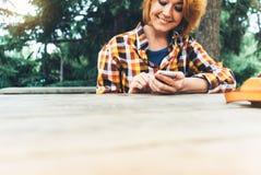 使用电话技术互联网,女孩人的行家女孩拿着在背景Sun City,女性手发短信的流动智能手机 免版税库存图片