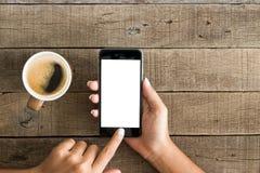 使用电话白色屏幕的手在顶视图 库存照片