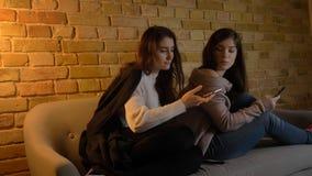 使用电话的两个年轻俏丽的白种人女孩特写镜头画象,当基于长沙发户内时 一分享的a 免版税库存照片