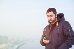 使用电话的人旅客反对冬天都市风景 图库摄影