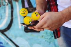 使用电话的人送emojis 免版税图库摄影
