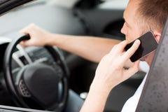 使用电话的人,当驾驶汽车时 免版税库存图片