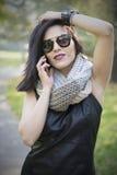 使用电话的可爱的黑发妇女 免版税库存照片