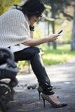 使用电话的可爱的黑发妇女 免版税库存图片