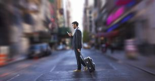 使用电话的商人和拿着手提箱反对城市背景 免版税库存图片
