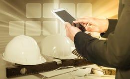 使用电话的商人在安全帽背景 免版税库存照片