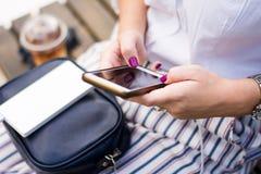 使用电话的女孩,当充电在力量银行时 免版税库存图片