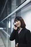 使用电话的女实业家由玻璃墙,北京 免版税库存图片