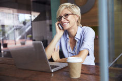 使用电话的女实业家研究膝上型计算机在咖啡店 图库摄影