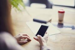 使用电话的女实业家,当坐在他的有木桌的时办公室 布局的,流动屏幕空的空间 免版税库存图片