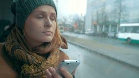 使用电话的妇女在公共汽车在雨天 影视素材