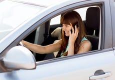 使用电话的妇女,当驾驶汽车时 免版税库存照片
