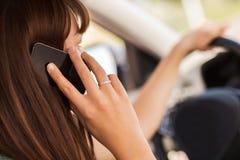 使用电话的妇女,当驾驶汽车时 免版税库存图片