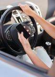 使用电话的妇女,当驾驶汽车时 库存图片