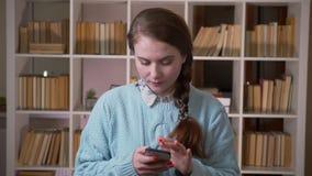 使用电话的年轻俏丽的女生特写镜头画象看照相机在大学图书馆户内 影视素材