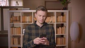 使用电话的年轻可爱的白种人男生特写镜头射击在大学图书馆 影视素材