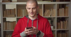 使用电话的年轻可爱的白种人男生特写镜头画象在大学图书馆户内 股票视频